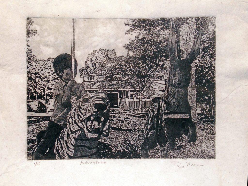 Boy on carousel tiger beside a carousel hare
