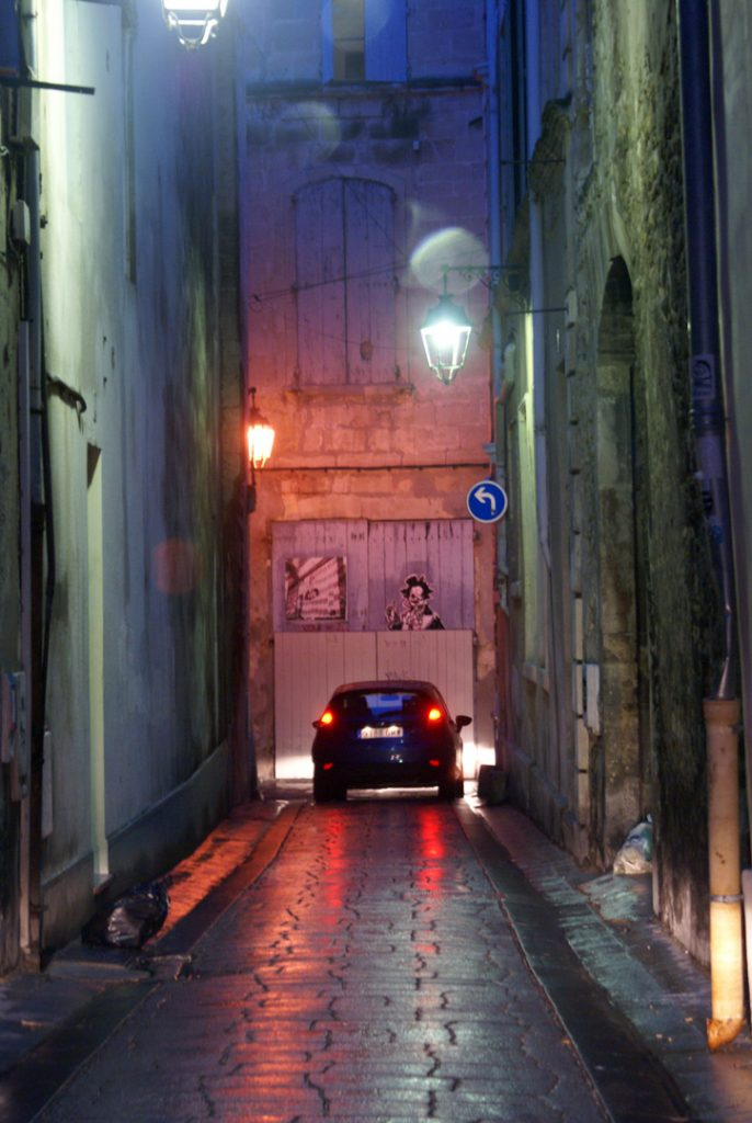 A narrow alleyway in Isle sur la Sorgue, Provence, France on a colorful but damp evening