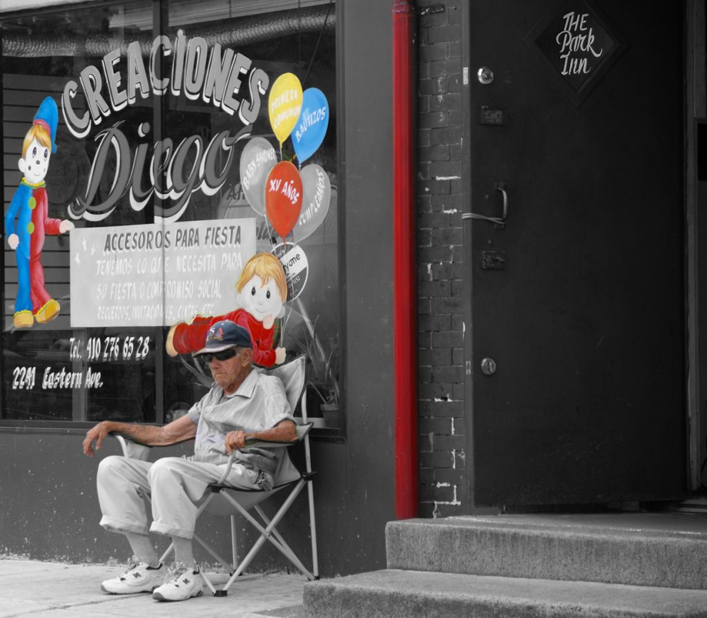 Senior Citizen in a folding chair in front of a fiesta shop on Eastern Avenue, Baltimore
