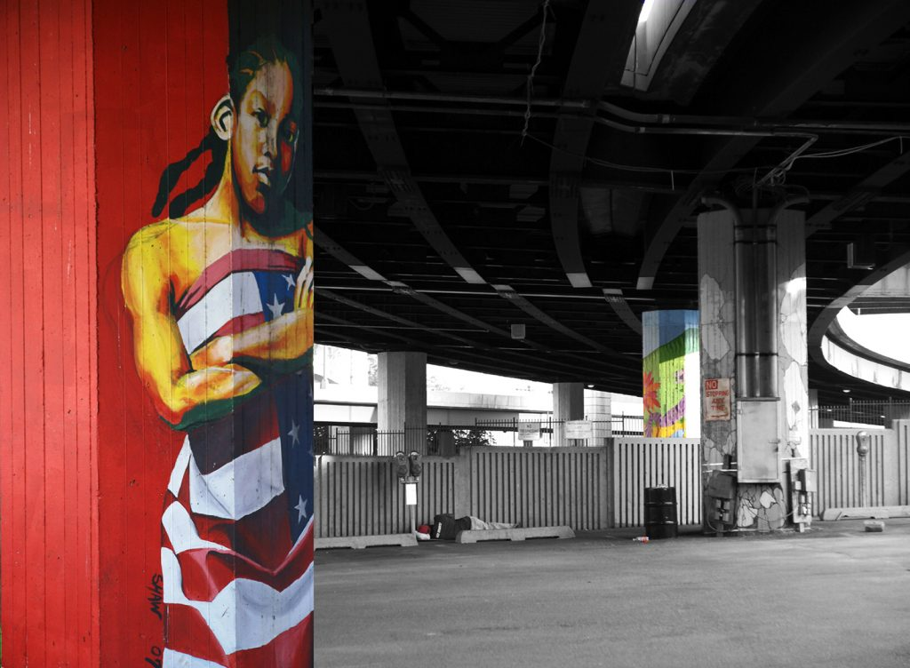 Independence day, under the Jones Falls expressway,  pillars painted by artists, homeless person sleeping