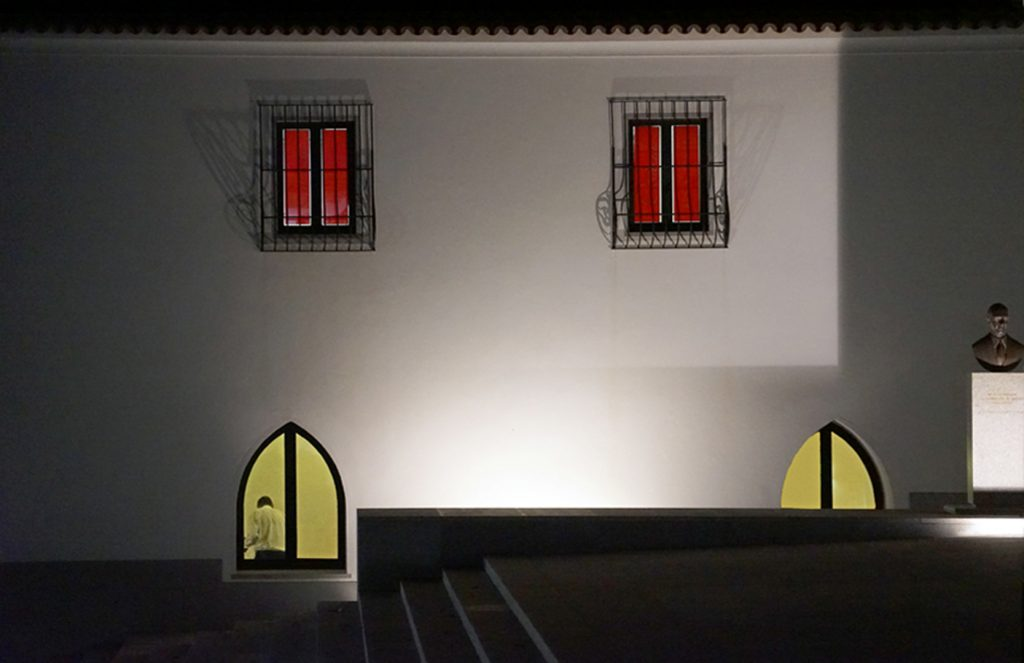 Evore, Portugal black stone walkway, white stucco wall with yellow window with a man working very late.  Upstairs barred window with red blinds.