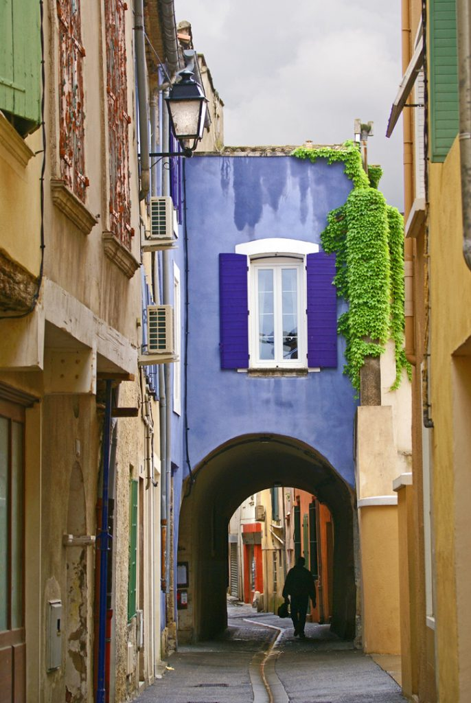 A back street purple archway with damp tan stucco walls and light green shutters and ivy